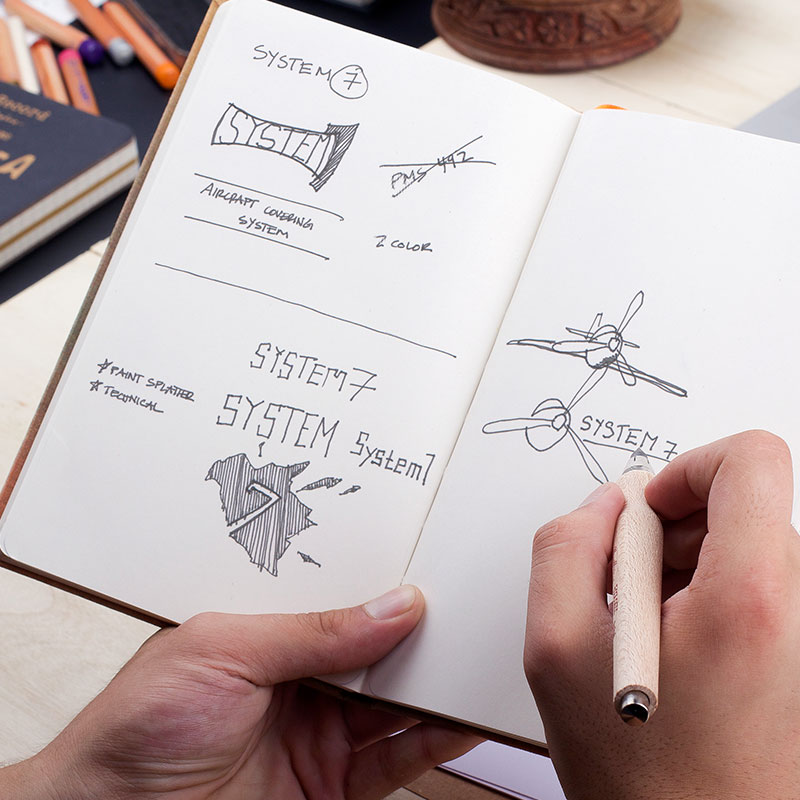 Image of a hand that's sketching out logo concepts for the Superflite System 7 aircraft covering system